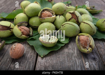 Group of fresh green walnuts on wooden table, autumn harvest - Stock Photo