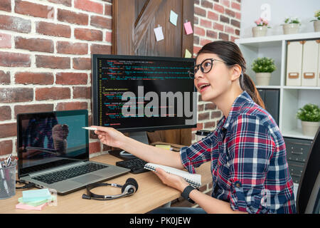 young beautiful programmer displaying codes on screen and representing confidently. - Stock Photo