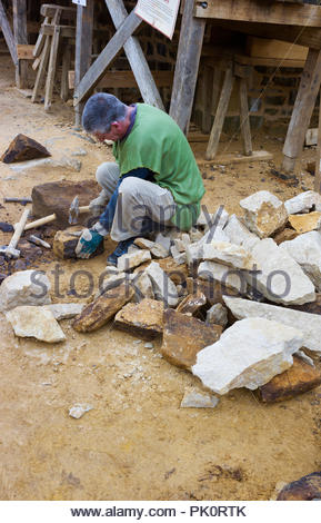 A stonemason working at Gudelon Castle, Burgundy, France. The castle is being built entirely using medieval tools and building methods. - Stock Photo