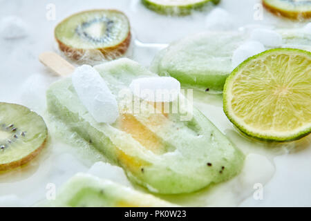 Homemade ice cream on a stick with a piece of peach. Pattern from splashes of pieces of different fruits, ice and melting ice cream on a gray backgrou - Stock Photo