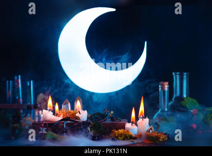 Halloween header with shining full Moon. Witch or wizard workplace with burning candles. Spooky still life concept on a dark background with copy spac - Stock Photo