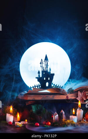 Halloween concept with a haunted castle silhouette in front of full Moon. Book of spells on witch or wizard workplace. Creative magical still life on  - Stock Photo