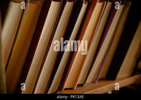 Many old books in a book shop or library. Toned image. .Selective focus.Antique books stack.Retro style.Vintage books on bookshelf.Concept of reading. school bench - Stock Photo