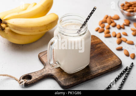 Banana protein smoothie in drinking glass on wooden serving board. Closeup view - Stock Photo