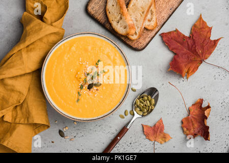 Pumpkin soup puree or cream soup in bowl. Autumn comfort food on concrete background. Warming bowl of soup - Stock Photo