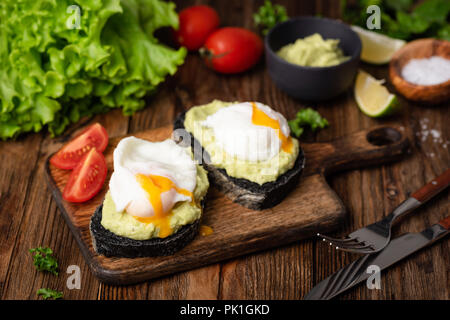 Healthy Tasty Toast With Avocado Poached Egg On Wooden Serving Board. Closeup view, selective focus - Stock Photo