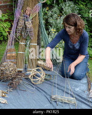 Small Willow sculptures are laid out in front of a variety of wicker stems with artist Sara Holden - Stock Photo