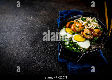 Traditional asian food, ramen soup with shrimp, noodles, spring onion, sliced eggs, mushrooms, on dark concrete background with chopsticks copy space  - Stock Photo