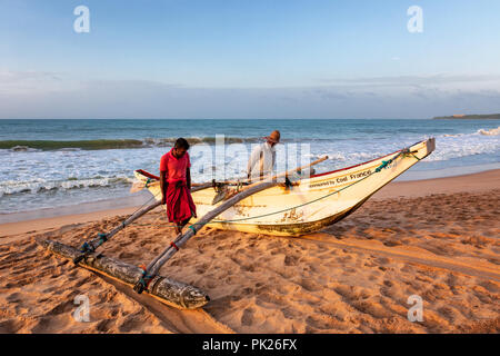Sri Lankan fishermen pulling out their boat at Kahandamodara Beach, Sri Lanka - Stock Photo