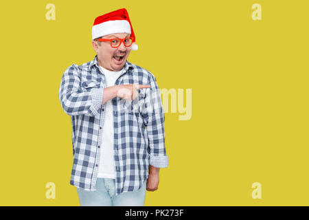 Positive middle aged man in red new year santa cap and casual style, standing, pointing finger to empty copy space and with suprised face, looking at  - Stock Photo