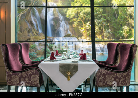 Luxury restaurant set over windows glass of the view of Beautiful waterfall in the forest, dicut each elements - Stock Photo