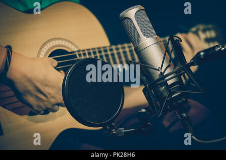 Professional condenser studio microphone over the abstract photo blurred of Closeup musician play the guitar, Musical instrument Concept - Stock Photo