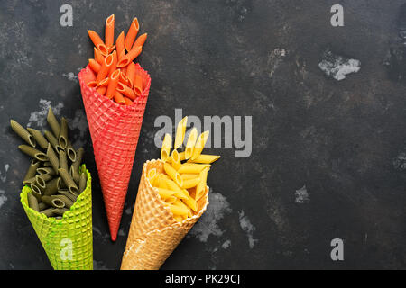 Colored pasta. Colored macaroni penne in waffle cones. The concept of nutrition. View from above, flat lay. - Stock Photo