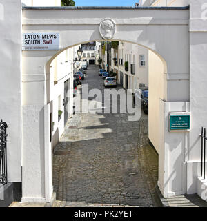 London street scene archway to narrow cobblestone mews homes with stone arch entrance Eaton Mews South Belgravia City of Westminster London England UK - Stock Photo