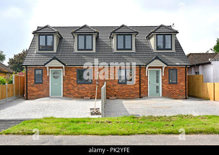 Front of new semi detached housing & home just completed house building paved over front garden car parking in existing suburban street Brentwood UK - Stock Photo