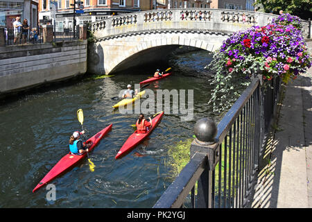 Kayak boats & group of four enthusiastic people passing under stone bridge Kayaking along River Can in Chelmsford town centre Essex England UK - Stock Photo