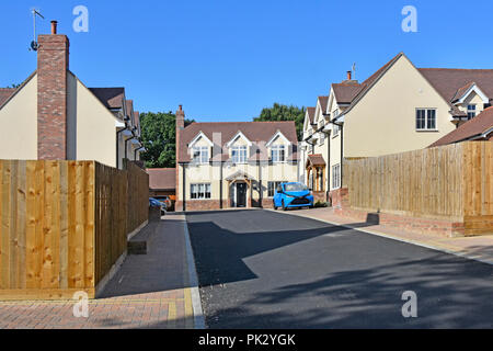 New home in housing property development mixed types real estate with tarmac service road garden fence & car parking space Essex England UK - Stock Photo