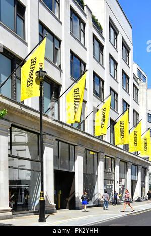 London shopping street scene yellow banner above Duke Street annex building behind the famous Selfridges department store in Oxford Street England UK - Stock Photo