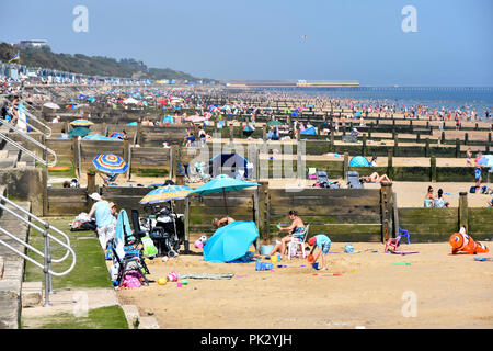 2018 hot weather summer crowds of holiday people on Essex seaside sand coast family beach for safe play & sunbathing Frinton on Sea resort England UK - Stock Photo