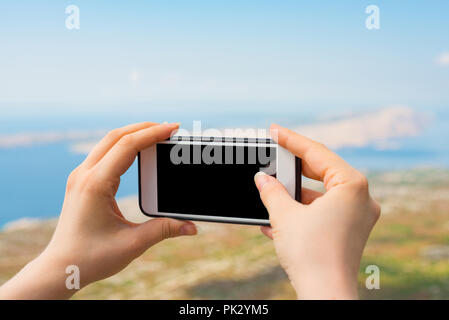 Female hands taking a photo of the landscape. Cropped shot view of woman's hands holding smart phone with blank copy space screen for your photo. - Stock Photo