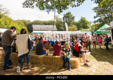 St Fagans, United Kingdom -  July 14, 2017: People sit eating on hay at the Food Festival in St Fagans, Cardiff, Wales - Stock Photo
