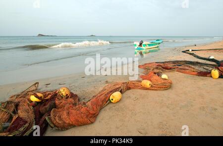 Small fishing boat and fishing nets on Nilaveli beach in Sri Lanka Asia - Stock Photo