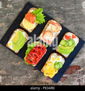 Of different sandwiches on the old wooden background. Top view. Flat lay. - Stock Photo
