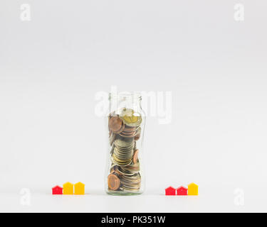 Investment Savings: Growing money for Home Loan Concepts: Full Coins in Clear Glass Bottles with a Small House or Hotel on a White Background include  - Stock Photo