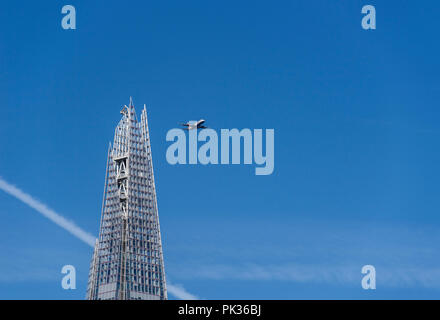 Low flying passenger plane close to the Shard on its final approach to landing at London City Airport, England, UK - Stock Photo