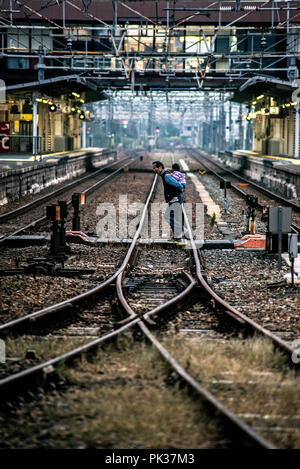 Shin-Kurashiki Station, Tamashima, Japan - November 18, 2015: A Japanese father crosses the railway with his child in his arms, on his back. - Stock Photo