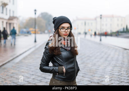 Fashion look.glamor lifestyle brunette woman model in black leather jacket and a black knitted cap outdoors in the street. - Stock Photo