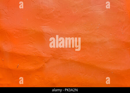 Concrete wall painted in orange paint, textured surface for backdrop. - Stock Photo