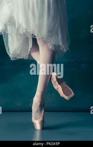 Close-up classic ballerinas legs in pointes on the gray wooden floor. Ballerina project with caucasian model. The ballet, dance, art, contemporary, choreography concept - Stock Photo