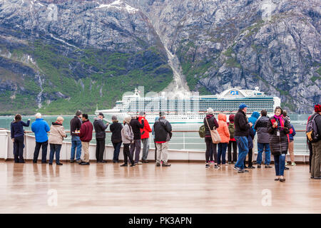 Passengers on the Holland America Line Cruises 'Nieuw Amsterdam' watching the passing by of Princess Cruises 'Ruby Princess' in the Tarr Inlet of Glac - Stock Photo