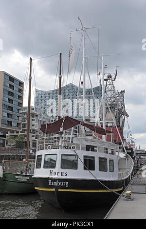Houseboat in Sandtorhafen in front of the Elbphilharmonie in Hamburg, Germany. - Stock Photo