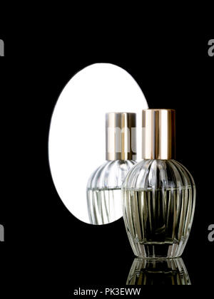 Elegant clear glass perfume bottle on a shiny black background with reflection also in mirror behind. With copyspace. - Stock Photo