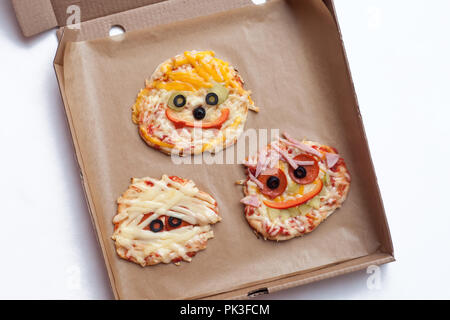 Halloween pizza with monsters, above scene with decor on a craft paper box background, idea for home party food, easy, healthy and delicious fun food  - Stock Photo