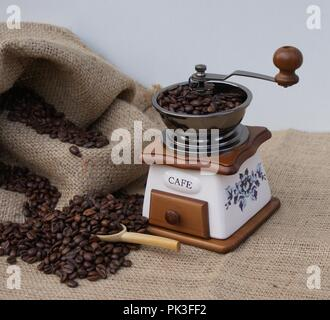 Closeup of a nostalgic coffee grinder next to a coffee bag with a wooden scoop for filling the coffee beans - Stock Photo