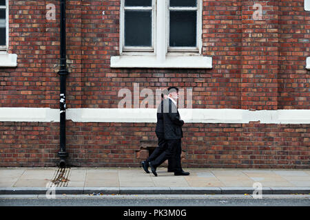 A man dressed in black with a white beard walks along the pavement with his partner. - Stock Photo