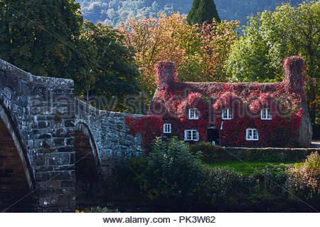 Betws-y-Coed, Conwy, North Wales - October 4, 2015: Tu Hwnt Ir Bont 15th century former courthouse now tearooms, and an old stone bridge in beautiful - Stock Photo