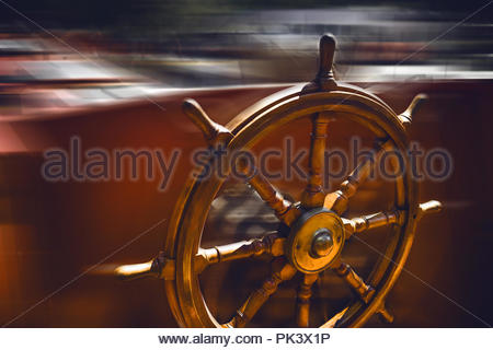 Abstract blurred antique wood and brass ships steering wheel. - Stock Photo