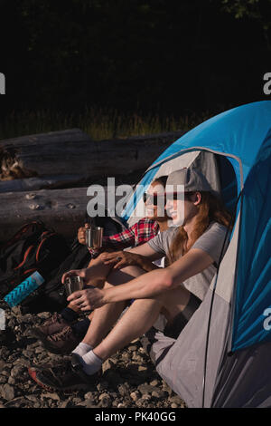 Couple relaxing in tent at countryside - Stock Photo