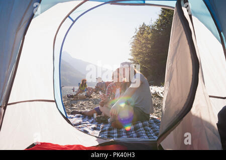 Couple relaxing near tent in countryside - Stock Photo