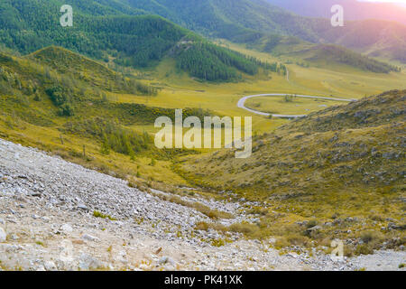 Landscape of the ridge covered with green trees and stones and view a valley flooded with sunlight, pasture, with dense clouds in the sky. Autumn day  - Stock Photo