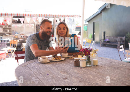 Couple taking selfie on mobile phone in outdoor cafe - Stock Photo