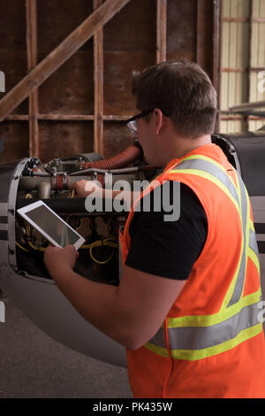 Mechanic using digital tablet while servicing aircraft engine - Stock Photo