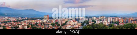 Golden hour large panorama cityscape, first autumn colors and distant horizon mountain under colorful sky - Stock Photo