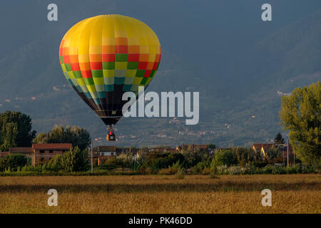 Colorful hot-air balloon flies over typical village in the Tuscan countryside in the light of the sunset - Stock Photo