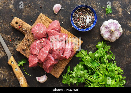 Raw beef pieces on a wooden Board with spices. The view from the top,flat lay - Stock Photo