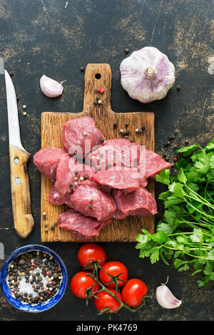 Pieces of raw beef meat with spices and cherry tomatoes on a dark background. View from above, flat lay. - Stock Photo